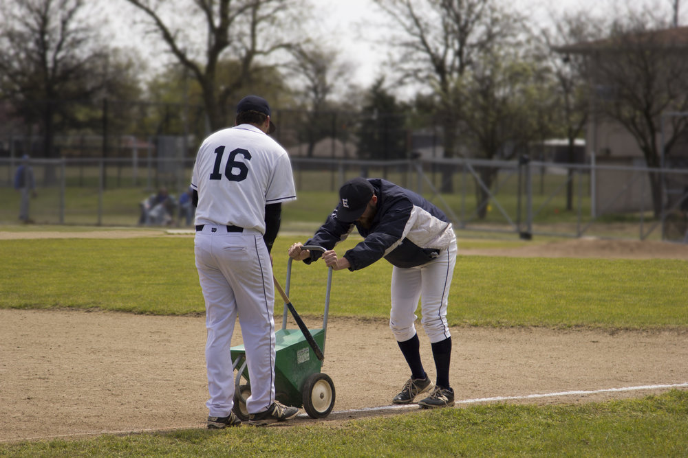 EC pitcher Daryl Rivera and EC player Nick Drago prepare baseball field for a double header on Saturday, April 22.  Photo by Cole Sheeks