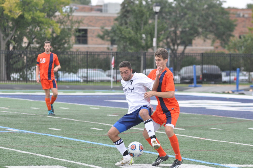 An EC men's soccer player battles for possession at Langhorst Field.  File Photo