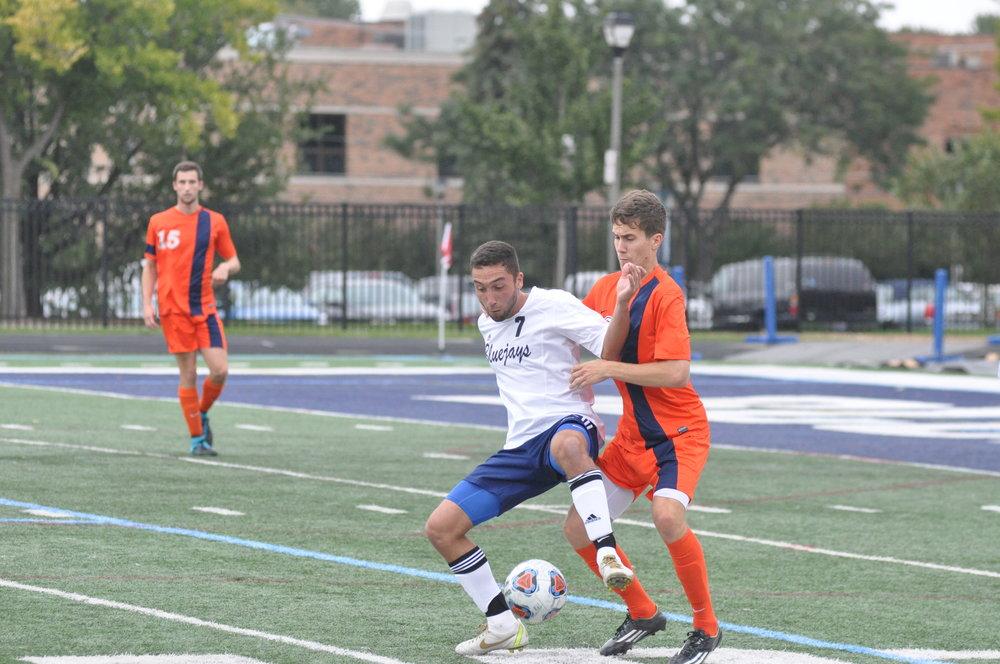 An EC men's soccer player battles for possession at Langhorst Field. File Photo
