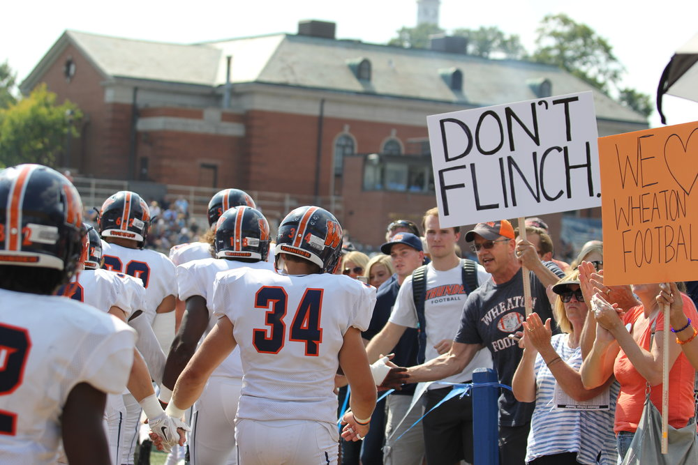 Photo by Cole Sheeks   The Wheaton College football team takes the field on Saturday, Sept. 23 holding hands, greeted by fans holding signs to show support for the team during the hazing scandal.