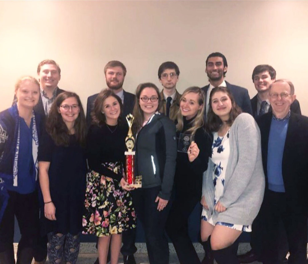 Photo courtesy of Mary Walsh   The EC mock trial team poses with their trophy after taking second place at the Midwestern regional tournament.