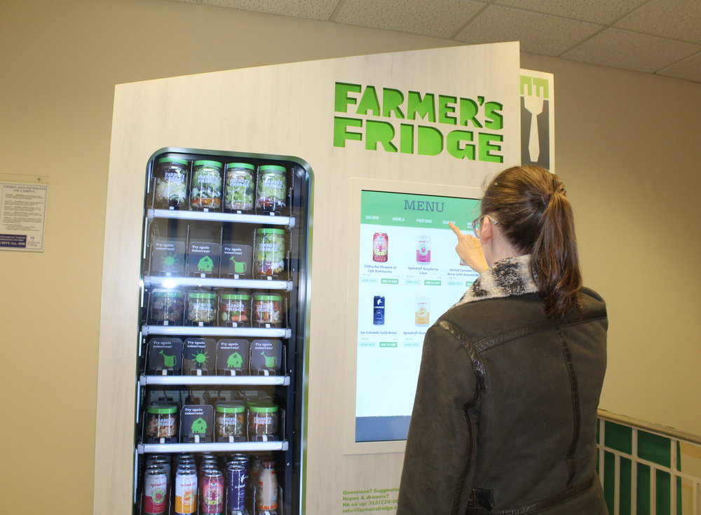 Photo by Abby Robb   An EC student makes a purchase from the Farmer's Fridge vending machine in the Frick Center.