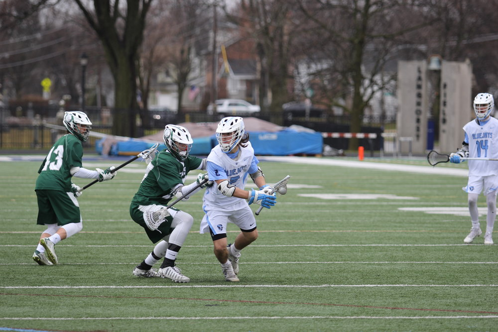 Photo by Cole Sheeks Bluejay junior Mac Harden looks for open field near the net against Illinois-Wesleyan on April 15.