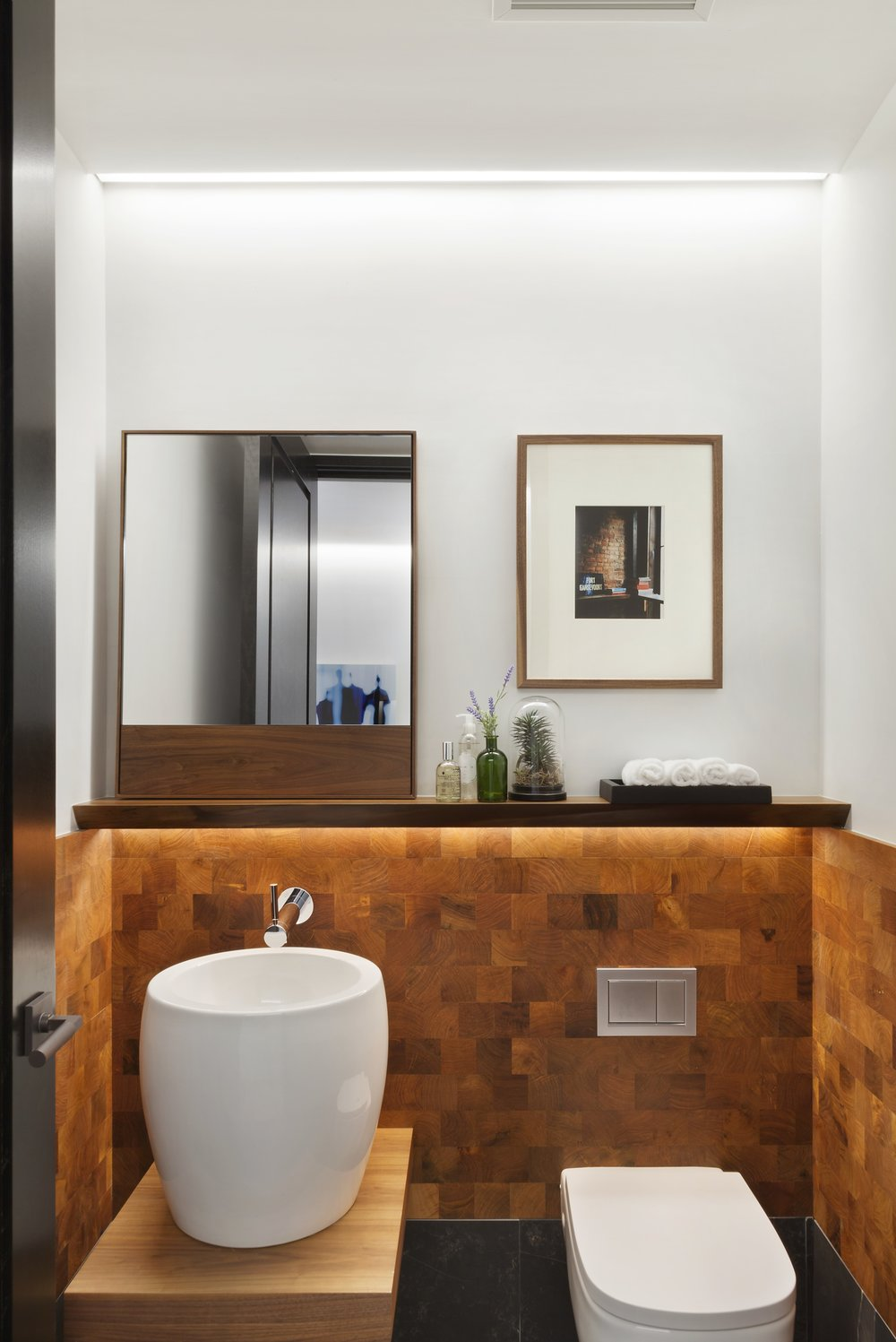 We loved designing this powder room, the basin sink surrounded by beautiful wood wall tiles result in a tranquil, almost zen effect. Bathroom designed by ODA Architecture