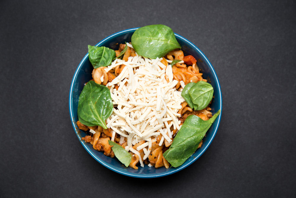 Pasta with Tomato sauce and fresh red & yellow peppers with Veggie Ground Round and spinach and vegan cheeze