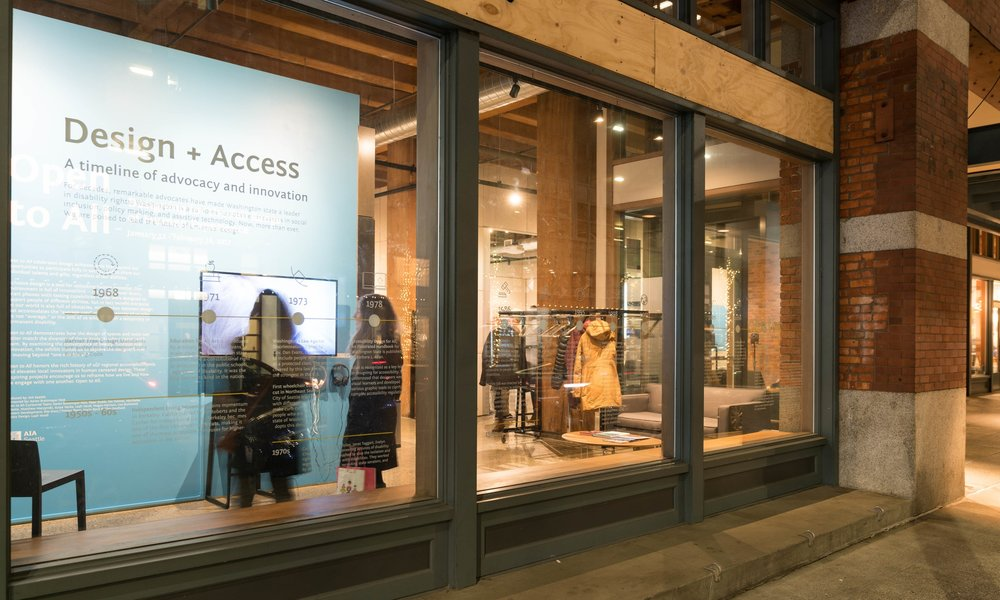 "A front window to the Center for Architecture and Design in Seattle displays the words ""design and access, a timeline of advocacy and innovation"". People inside the studio are watching a video on a screen."