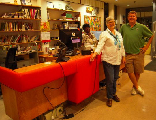Head librarian Anne Smart and FOSEL board member Glyn Polson at newly refurbished library counter; library clerk Deborah Madrey is behind the counter.