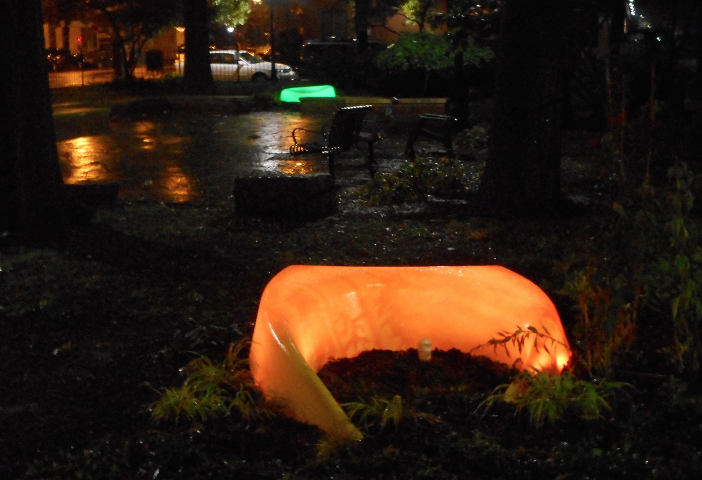 Two LightWells lit up in Library Park at night, seen from the library building