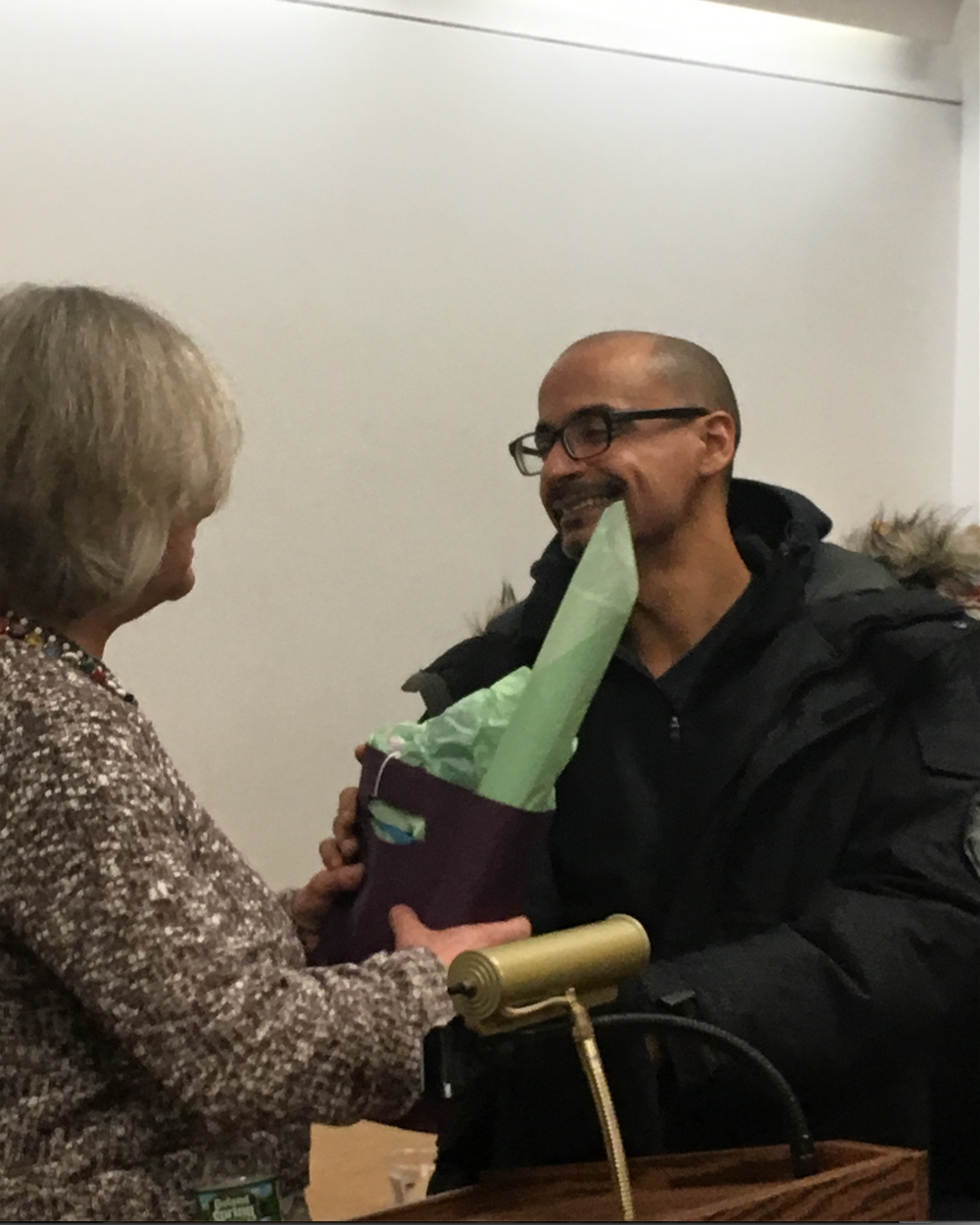 Junot Diaz receives the traditional FOSEL gift of a FOSEL library bag and copies of his event poster