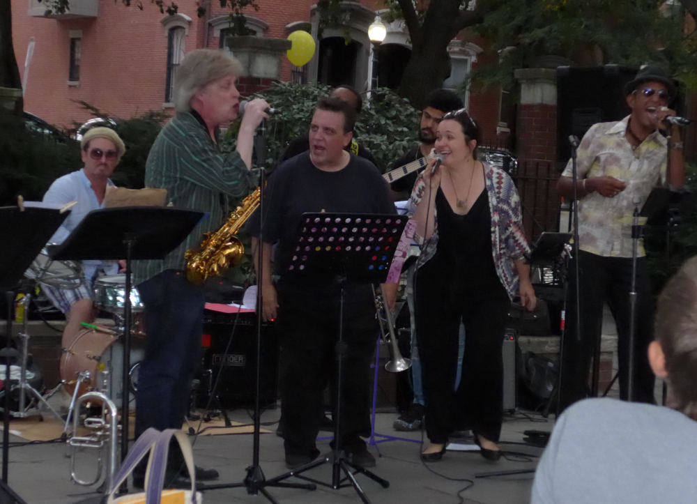 Benny Benson, drums; Pat Loomis, singing with Sax in hand; Scott Aruda, singing with trumpet; Christoff Glaude, bass; Antonio Loomis, guitar; Sarah Seminski and Nephtaliem McCrary, vocalists
