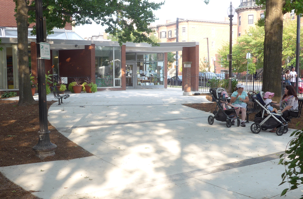 A broad plaza/walkway leads from the South End branch to the park entrance at Rutland Square. The chairs in the image were in good-enough condition to preserve for the newly improved park.