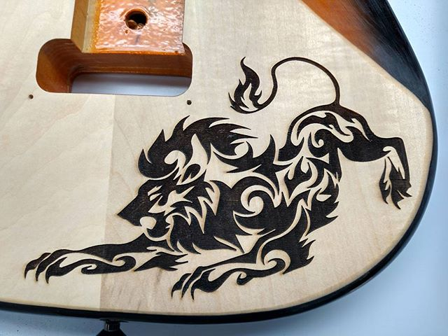 Custom laser etched lion on guitar back.