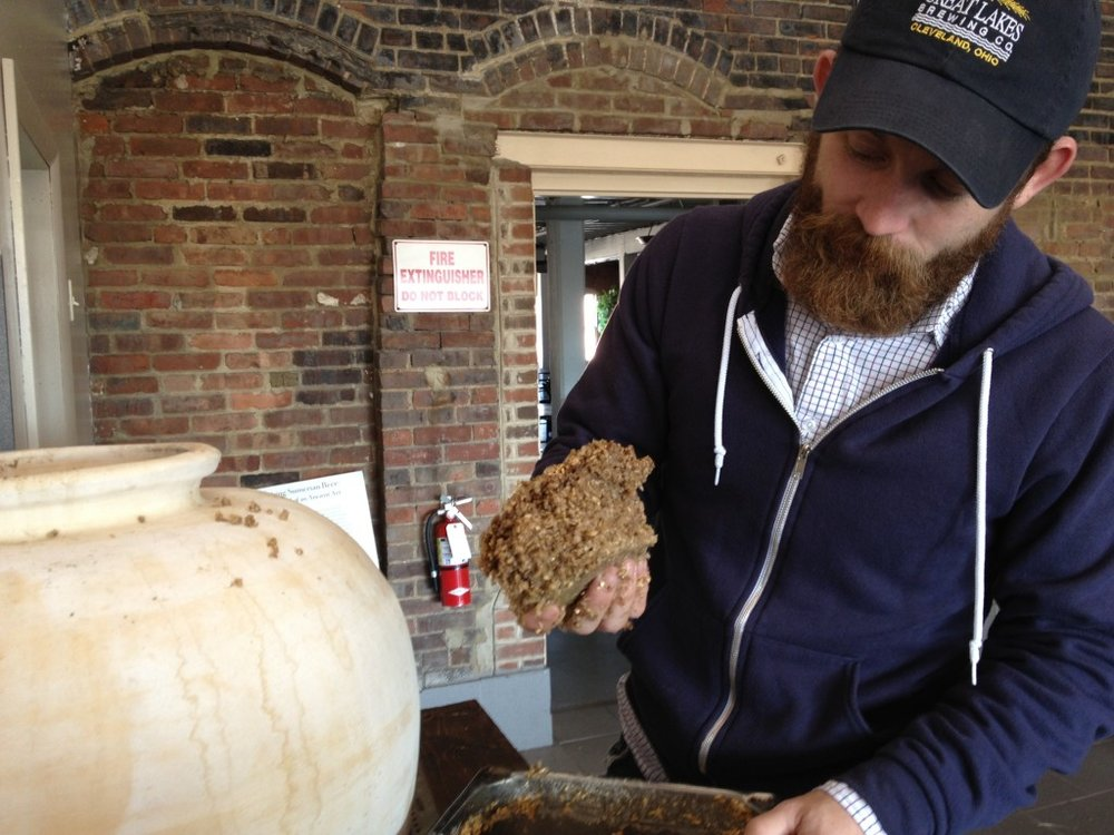 """Brewing Mesopotamian beer. A collaboration between the Oriental Institute (University of Chicago) and Great Lakes Brewing Co. (Cleveland, OH). Tate Paulette adds bappir or """"beer bread"""" to a ceramic fermentation vessel crafted by Brian Zimerle. (Photo credit: Brian Zimerle)"""