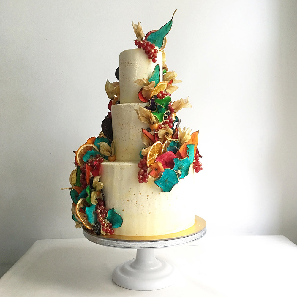 Our Signature AB Style - Three tiers of classic white cake decorated in our signature dehydrated dip died fruit petals & splattered in gold. Fruits can be died to match your wedding colours & are 100% edible. #edibleart