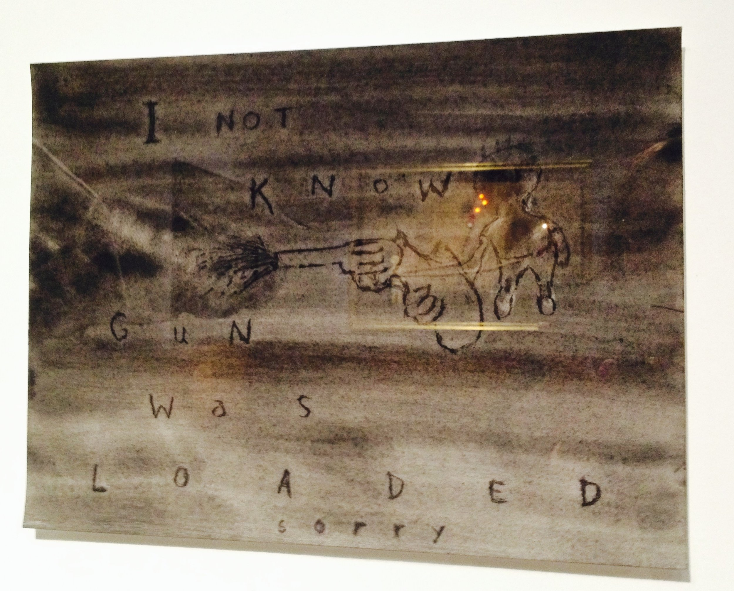 "A painting of a small child who shot a gun. The words read ""I not know gun was loaded sorry."" In the exhibition room ""Home."""
