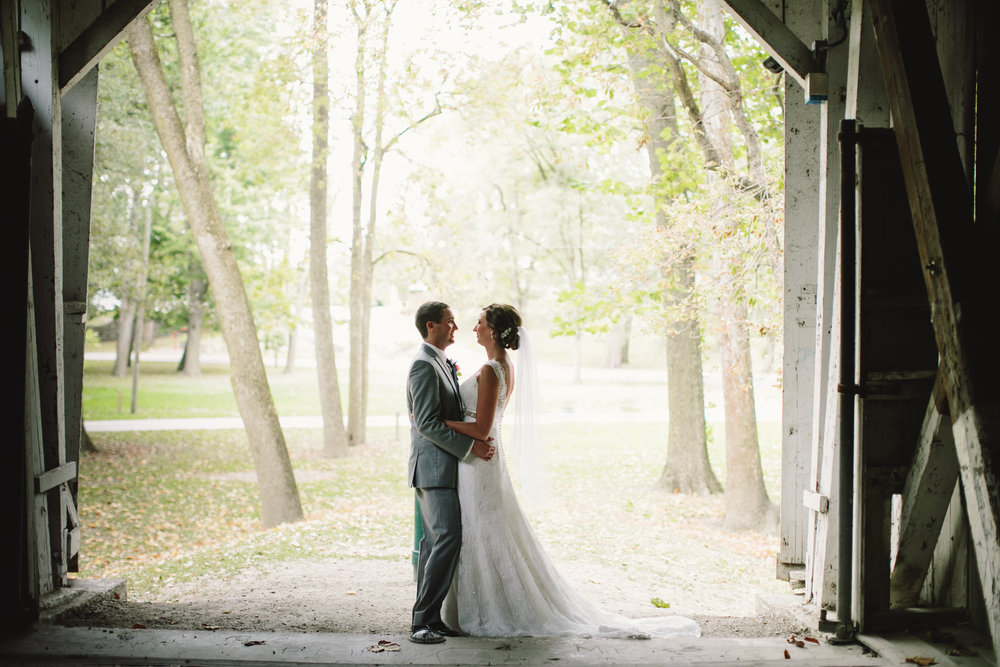 Bride and Groom embrace in light of barn doors at Rustic Wedding Reception
