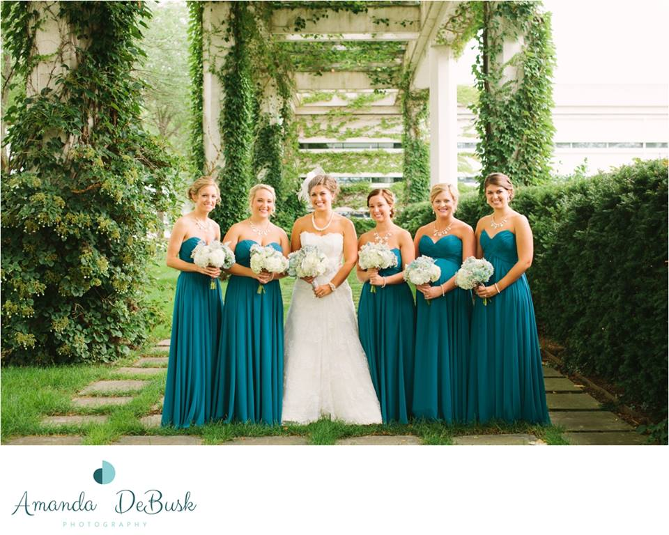 Bride & her Bridesmaids holding their bouquets outside in garden terrace