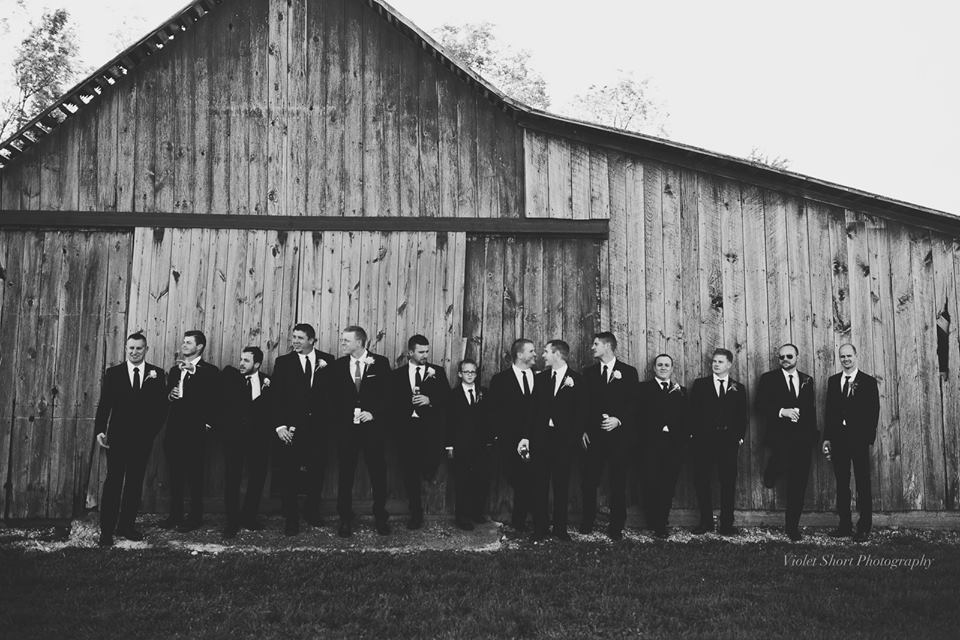 Groom and Groomsman lined up against the rustic backdrop of a barn