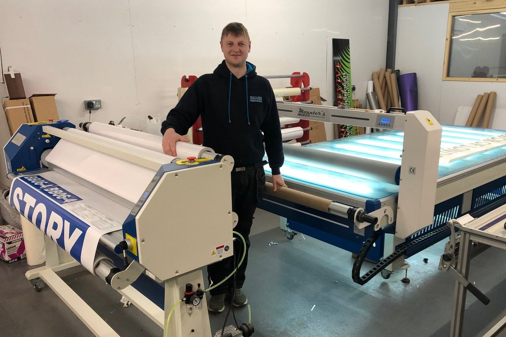 """A Mounter's Mate Workstation and a 1600hs laminator have boosted throughput at this busy sign maker on the borders between Scotland and the Lake District. """"It's been like going from a Fiesta to a Ferrari!"""" With the Workstation, he says """"We do quite a lot of hoarding work for one of our customers who's a builder. This is Dibond and foamex panels and that sort of thing. It was taking two men to cover panels and now it's become a one man job."""" - Will, Image Signmakers, Carlisle"""