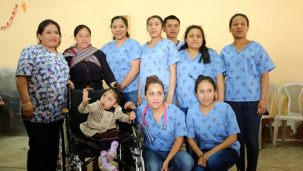 Iliana Sapón and her team of volunteers with the recipients of a wheelchair