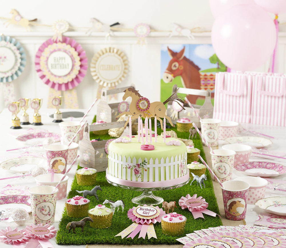 LUCY'S 8TH BIRTHDAY PONY PARTY This party focused on bringing the outdoor feel inside. A hessian table runner with a grass runner on top, really gave the table texture and the mini ponies and hay bales placed around the table were perfect for the theme. Other equestrian elements included mini trophies, tack boxes for snacks and rosettes and raffia garland decorations for the room. The pink floral and gold patterns on the tableware looked gorgeous and were perfect for an older girls party. This was the perfect pony party for Lucy and she awarded it first place!