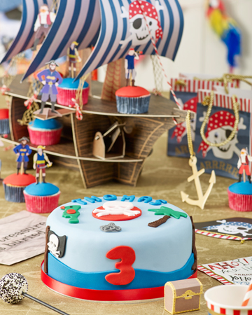 THOMAS' 3RD BIRTHDAY PIRATE PARTY To be a real pirate you need a ship and the centrepiece for this party was a fabulous galleon, complete with cannon, pirates and a gold anchor. It also happened to be a great display to put the cupcakes on too. The tablecloth was a giant treasure map and there were pirate hats with skull and crossbones for all to wear. Party games included Party Mums pass the parcel and a game of pin the patch on the pirate. When it was home time, party bags with gold rope handles and a skull image with googly eyes kept the theme going and goodies inside included pirate bubbles, pirate tattoo's, glider, parachute man, lollipop and a chocolate pirate. Thomas loved his party, so luckily we didn't have to walk the plank!