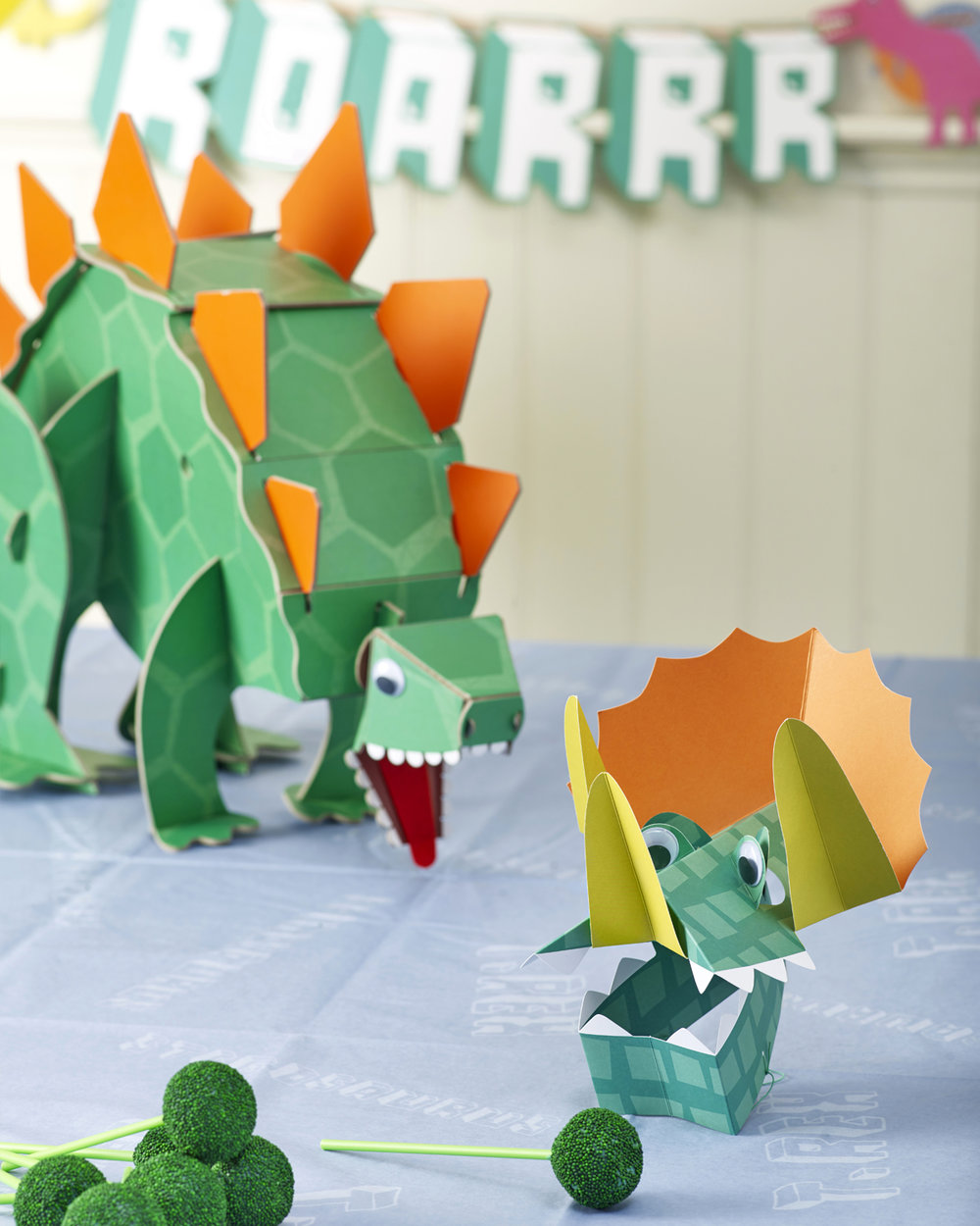 """GEORGE'S 1ST BIRTHDAY DINOSAUR PARTY  George absolutely loves dinosaurs, so it was very easy to pick a party theme to suit him. The Stegosaurus centrepiece was a big hit, with a wobbly head, googly eyes and a button to press that """"roared"""" loudly. This entertained all the guests during their lunch, which included cupcakes with 3D dinosaur toppers and cake pops in a coordinating green colour. The party hats were 3D triceratops with googly eyes that the guests just loved running around making dinosaur noises in!! Decorations included a bright coloured dinosaur banner that complimented the tableware and bright balloons with crepe streamers. A truly jurassic party suitable for any young budding paleontologist!"""