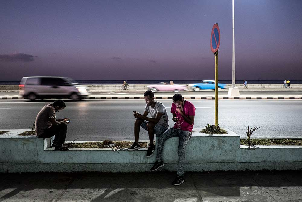 Youth surf the web alongside of Malecón highway in Havana, Cuba. © Moe Zoyari