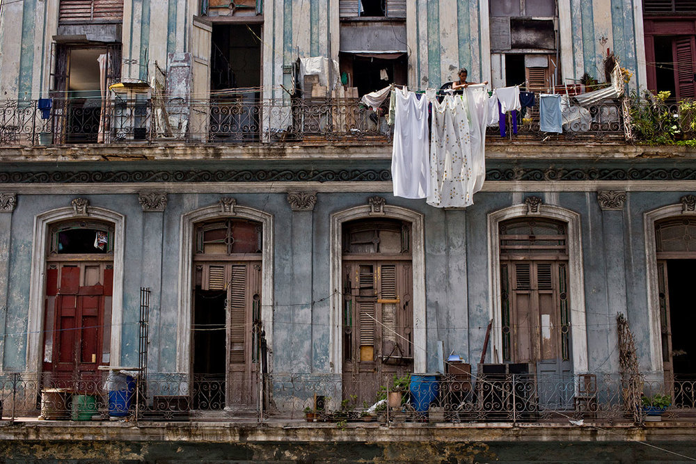 A woman hangs bed sheets to dry in Havana, Cuba.