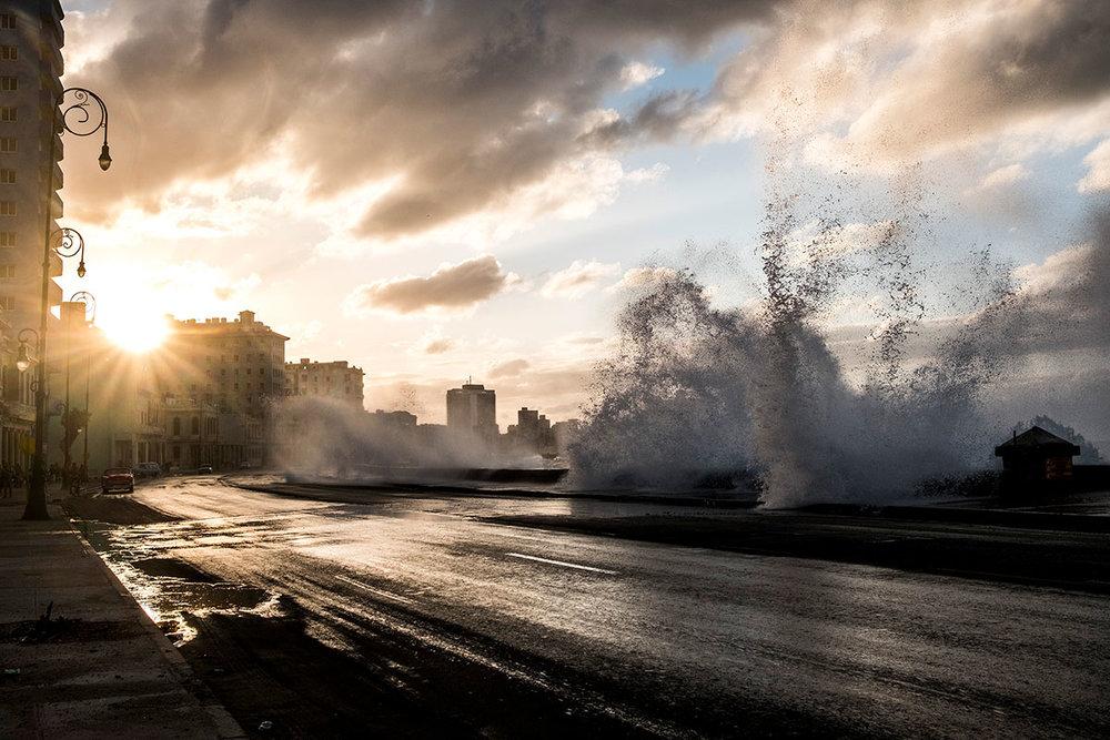 Waves crash over the Malecon highway as sun sets n Havana, Cuba.