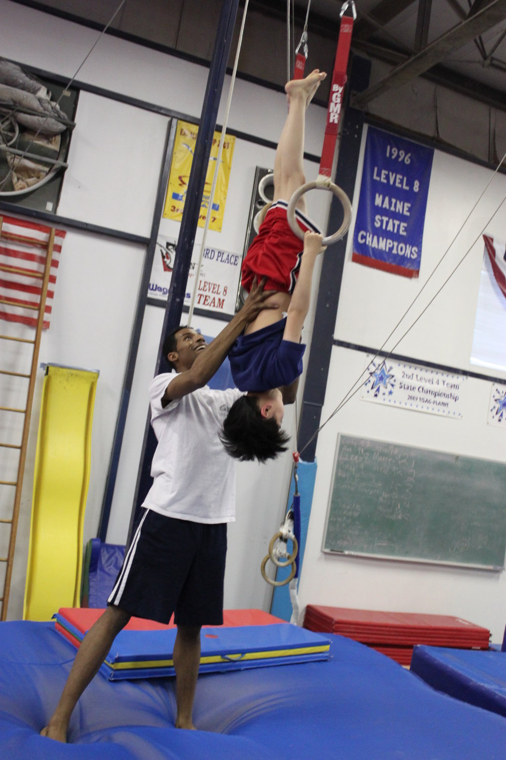 Boy on rings w: coach.JPG