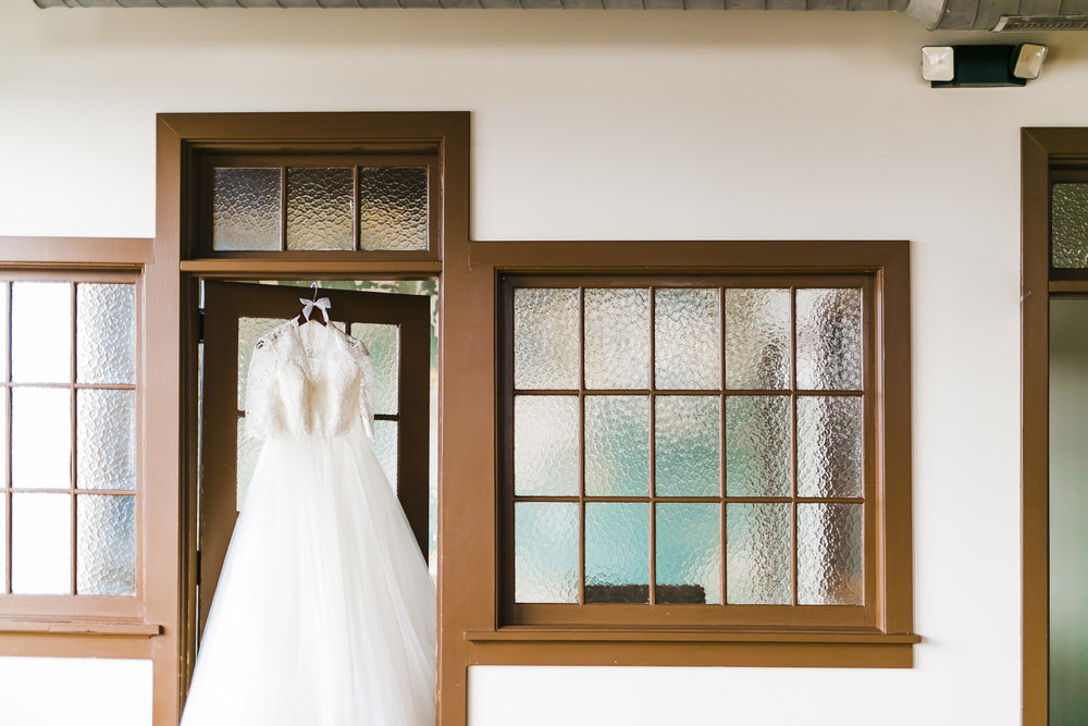 Classic ballgown with sleeves and lace hung in doorway of the standard knoxville bridal suite