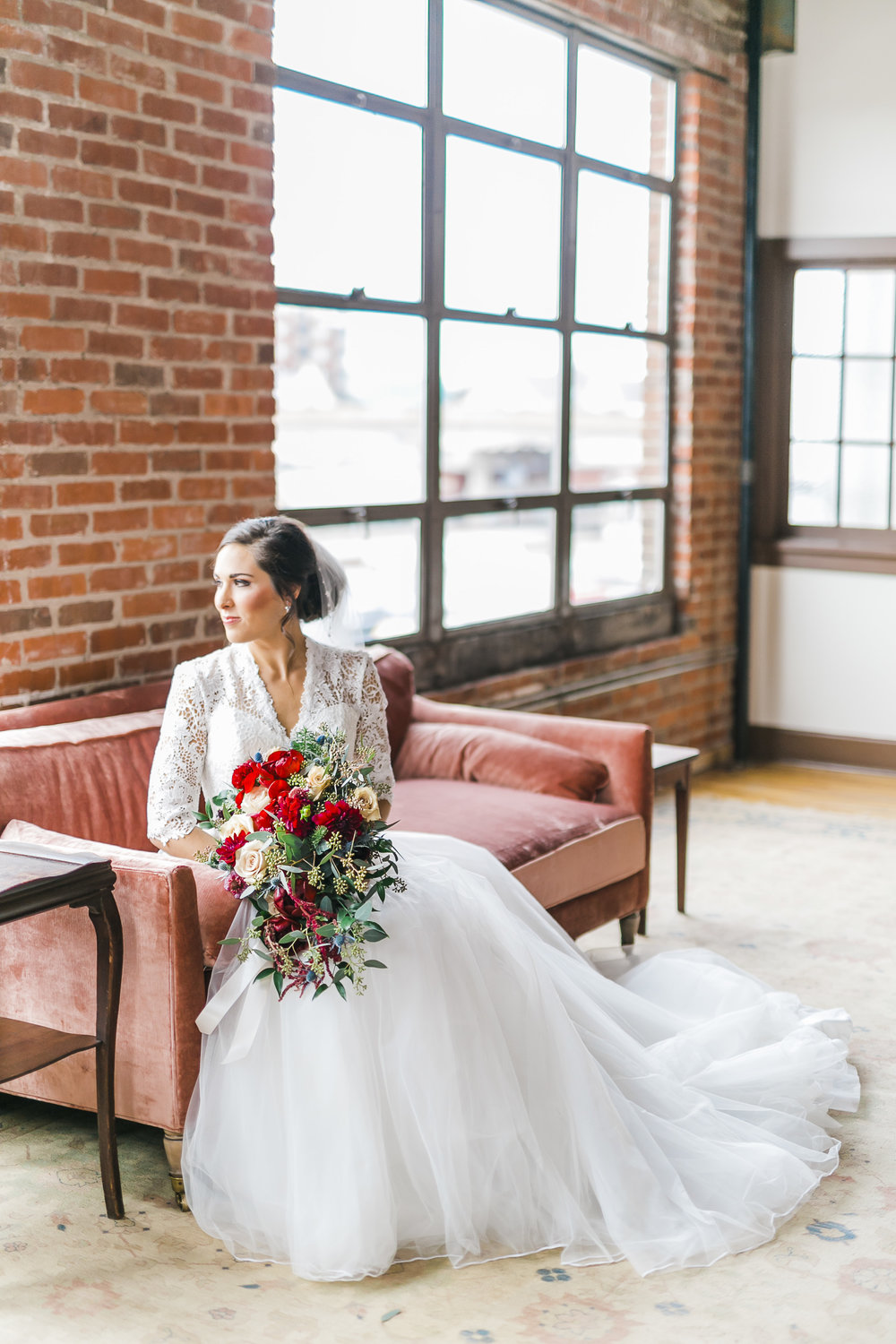 bride with ballgown and red and white flowers on pink velvet couch in brick room downtown knoxville with huge windows