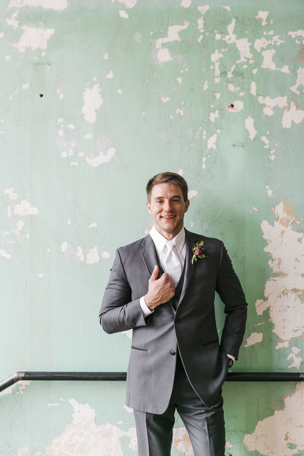 groom with grey suit against teal chipped wall in historic standard knoxville
