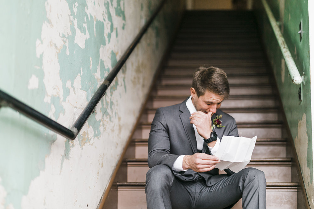 groom reading letter on stairs at the standard in downtown knoxville