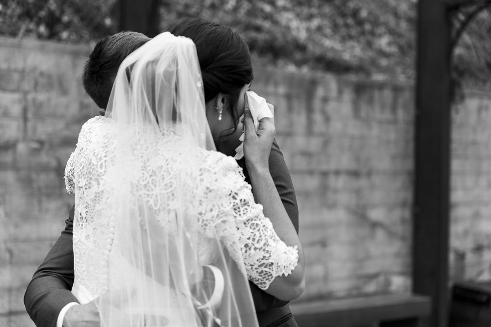 black and white of bride and groom first look bride crying