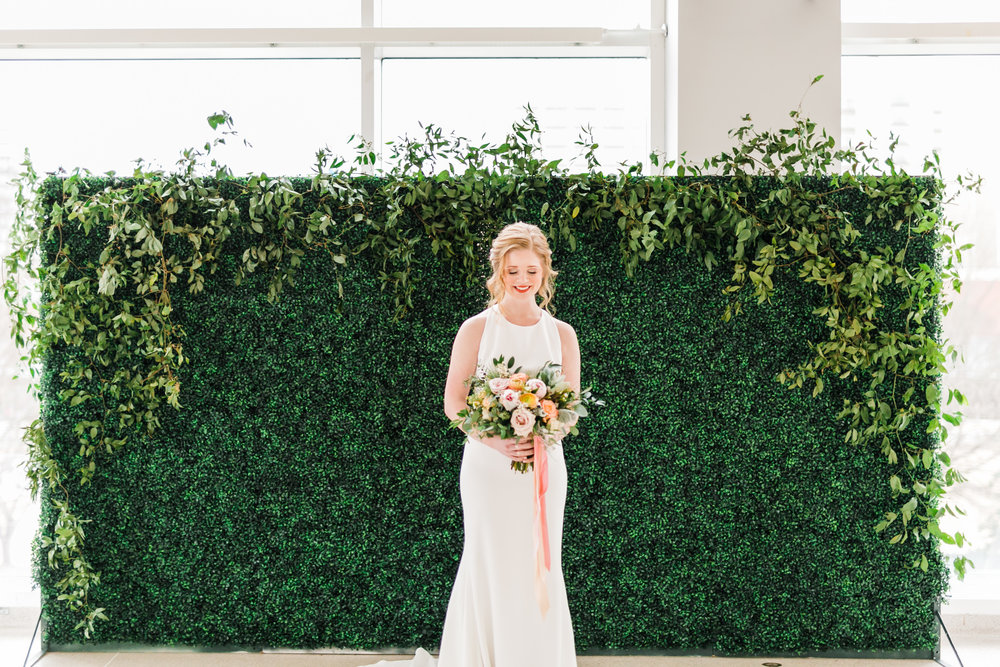redhead bride in front of greenery wall with pink and orange bouquet