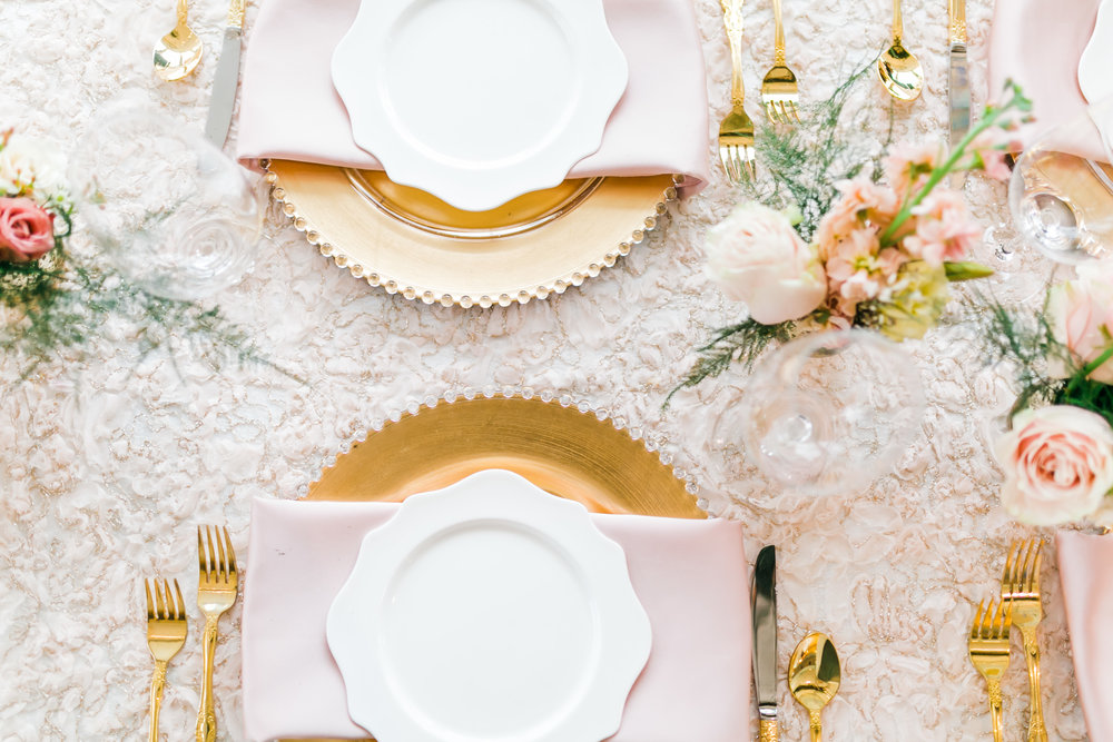 feminine table setting with gold charges and greenery and pink napkins