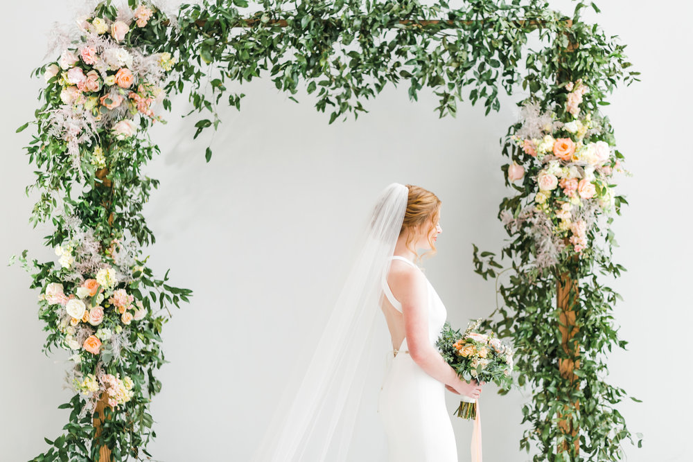 red head bride with veil under spring floral arch indoor at knoxville museum of art