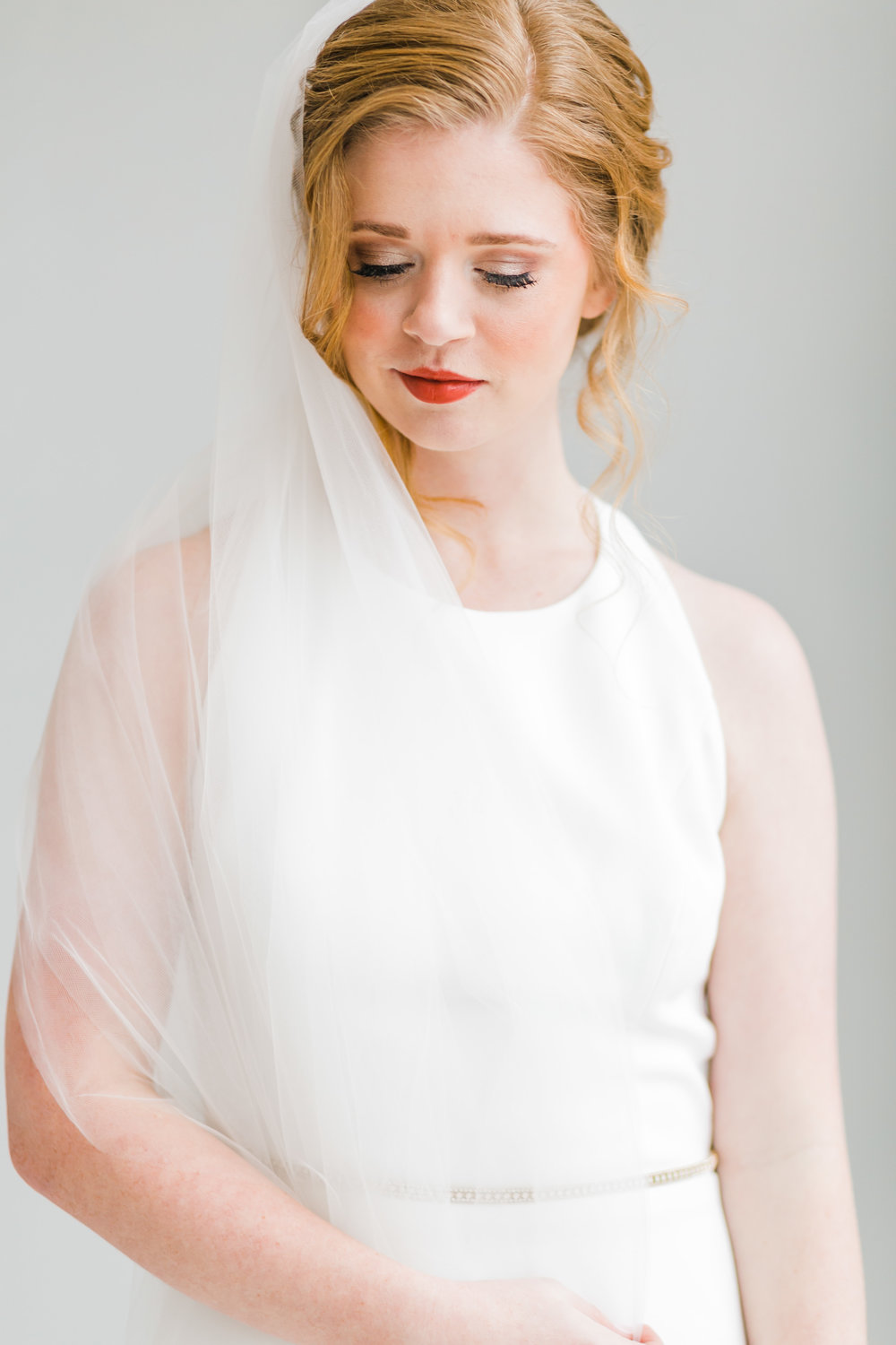 classic red head bride with unembellished dress pronovias and veil