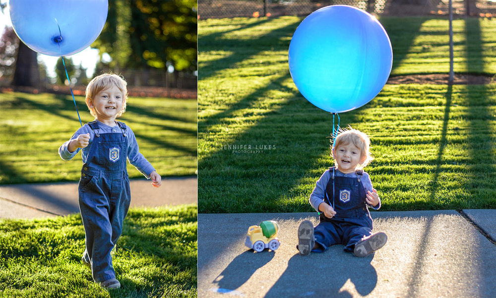 Toddler boy with balloon and toy truck in blue overalls.