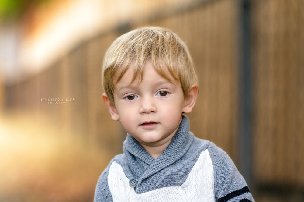 Close up photo of 2 year old boy wearing a gray shawl collar sweater.