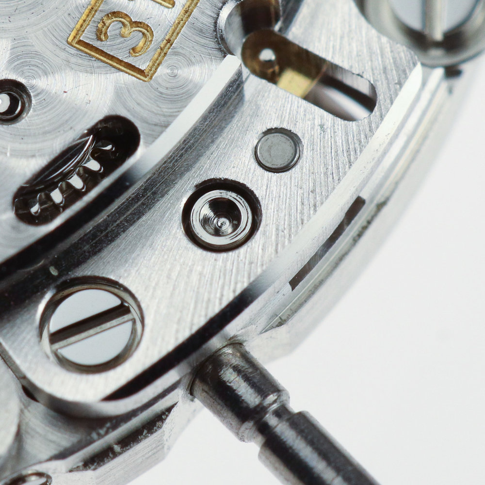 The button is part of the setting lever on the under side of the mvt holding the stem in place and linking to the setting mechanism.