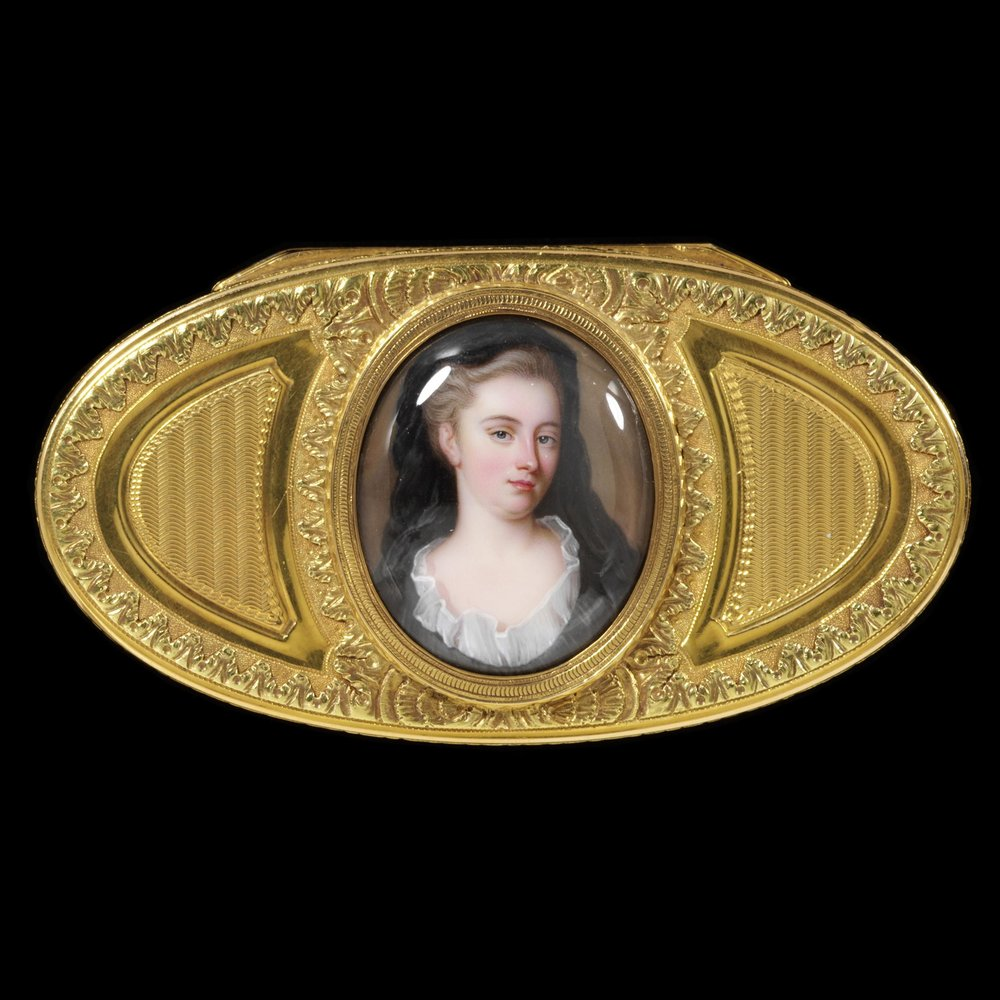 Oval varicoloured gold box, engine turned, chased and set with an enamel portrait of a lady by C F Zincke, dated 1717, Maker's mark for Charles Alexandre Bouillerot. Made in Paris, 1773-4  © Victoria and Albert Museum, London