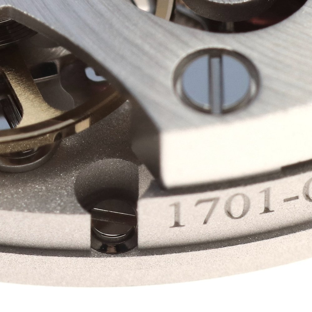 The lower screw is to fix in place the dial feet