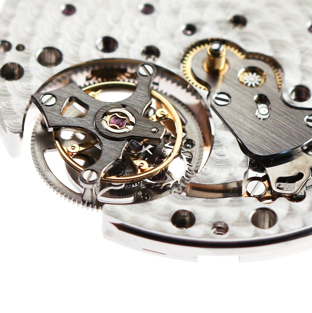 The cage is higher than the mainplate to allow the upper cage bridge to be flush with the dial when it is added