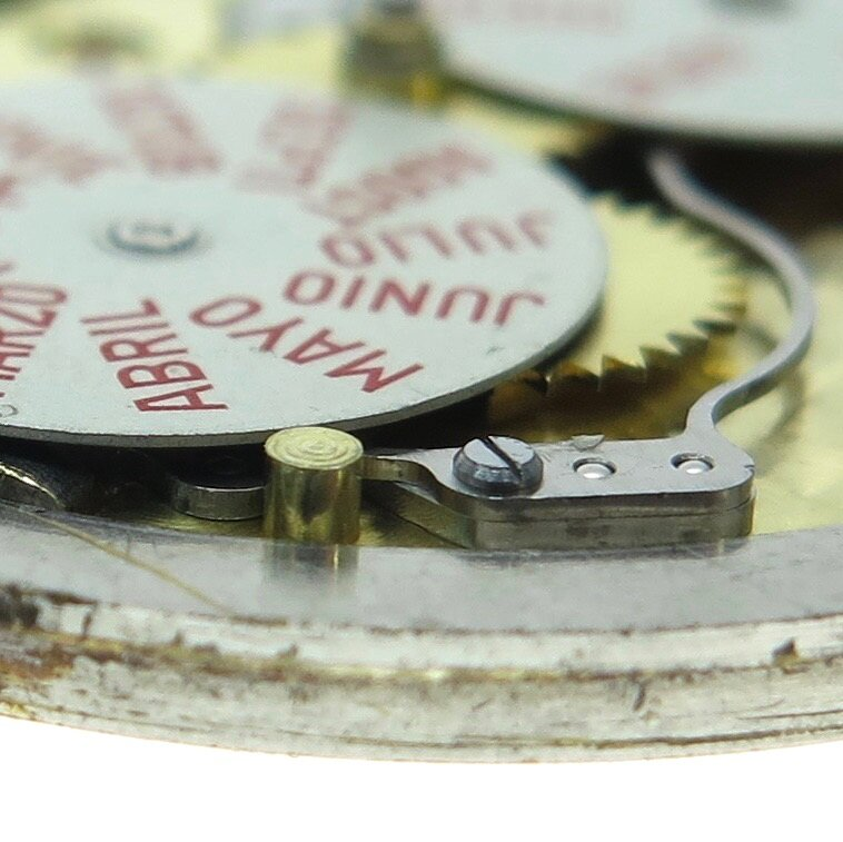 The large brass pin level with the month disc is a security to avoid the dial touching it