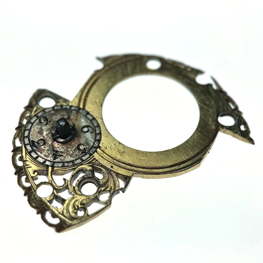 Regulating plate. The square section was turned and would link with the system to adjust the effective length of the balance spring altering the timing of the watch.