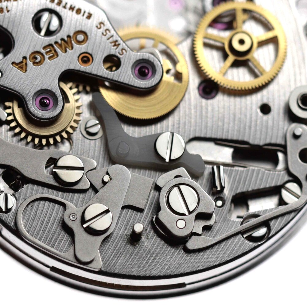 The central lever touching the chronograph seconds wheel is a type of plastic which acts a break when the chronograph has been manual stopped.