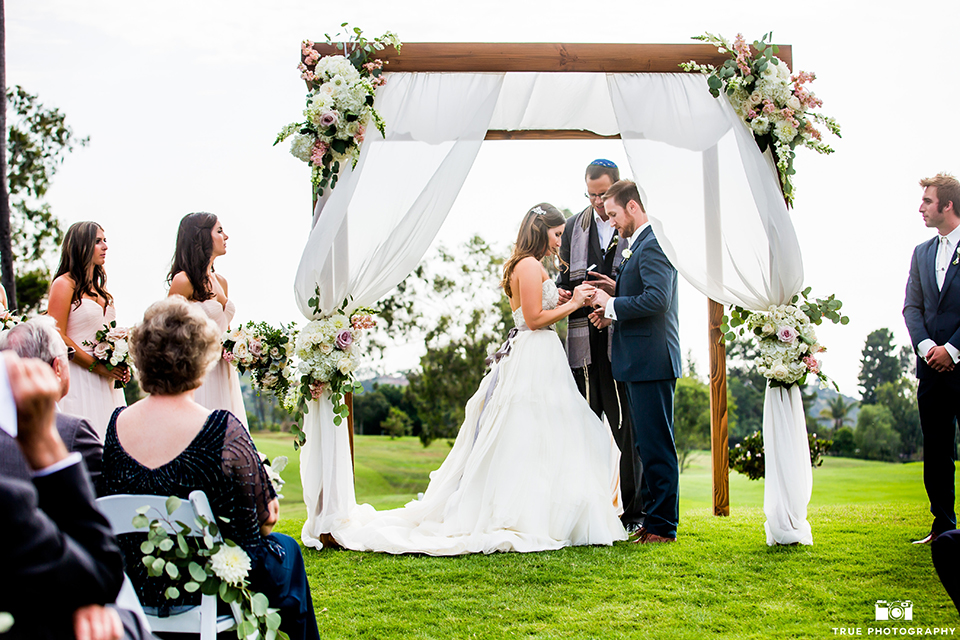 San-Diego-wedding-at-lomas-santa-fe-country-club-bride-and-groom-exchanging-rings.jpg